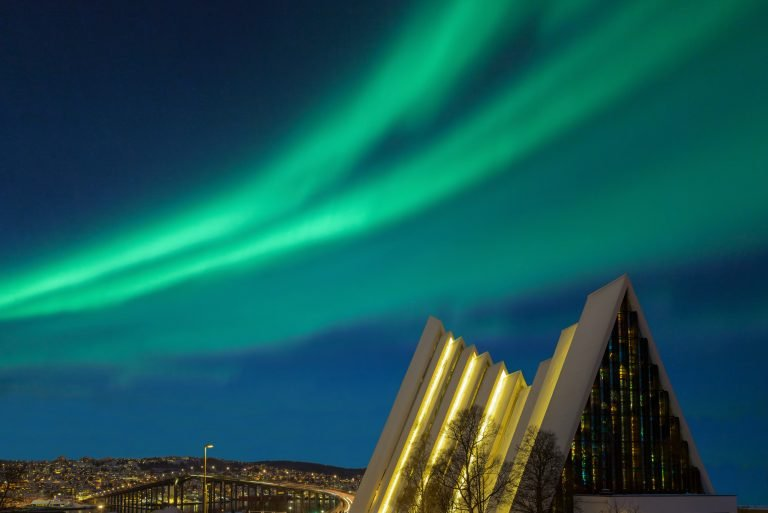 Illuminated Tromso cathedral at night with beautiful green shapes of aurora borealis